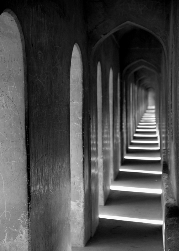 "Mosque Corridor #1, 2005. 10"" x 14"". Digital print on archival paper. The Imambara Mosque is rife with right angles, curved archways and more passageways than one could count. Hidden amongst the twists and turns, there is one true path to the open-air rooftop that overlooks the ancient city of Lucknow. Perhaps this is a metaphor for the one true path to spiritual enlightenment – if one can find the way..."