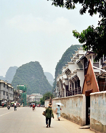 "Yangshuo Streetscape, 2002. 16"" x 20"". Digital print on archival paper. In an informal polling of friends and acquaintances, Yangshuo was hands down the primary destination recommended for a visit to southern China. With its limestone peaks, cheap hostels and cheaper food, Yangshuo proved to be a gathering place for Chinese and foreign backpackers alike. The streets were lively and the flat roads and rice patties offered a beautiful backdrop to a day of biking and hiking."