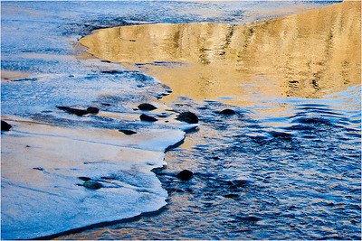 A little abstract ice and reflections on the water from the sunset on a rocky cliff behind the river....