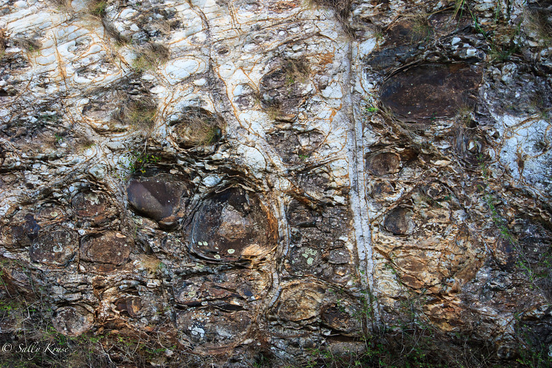 Rock face; shapes of faces in a rock wall.