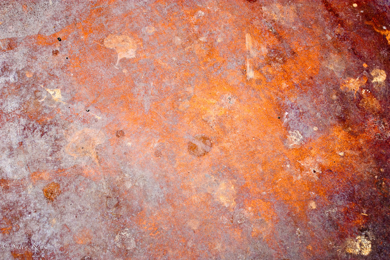 A rusty steel plate covering a hole in the street.