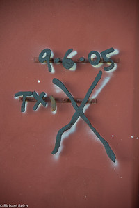 This design was found on the outside of a residence on the corner of Chartres St and Montegut St. (3001 Chartres St.) The owner of the home decided to put an iron outline over the spray painted symbol left by Katrina rescuers canvassing the city in the days after the hurricane. The X and the numbers around have to do with number of people in the house, how many living and how many dead. It was a way for rescuers to communicate with other rescuers.