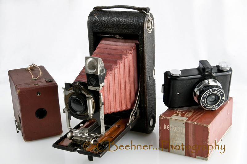 "10-30-2009…  Old, old cameras…<br /> <br /> The simple box camera as best I can identify it is a Kodak Hawk-eye No. 2, Model C.  Kodak produced this model from 1926 to 1934.  Somewhere along the line someone lost the handle and replaced it with some simple cord, I've left it alone.<br /> <br /> The 3A Folding Pocket Kodak, this one is a model B-4, Eastman Kodak's first postcard format camera, was introduced in 1903 and sold until 1915.  That puts this one in the ±100 year old range.  This one really had some features…the lens can be adjusted up or down and right and left from the film plane.  Shutter speeds of 100th, 50th, 25th of a second, Bulb and Timed, f-stops f4 to f128.  An optional glass focus plate was available and an air squeeze shutter release ""bulb"" could be used.  Sweet camera for its day…still is…<br /> <br /> Detrola Camera, Model A; Detrola (International Detrola Corp) was a radio and record-player manufacturer, based in Detroit, Michigan. They also made a few cameras, over a very short period they were in business - 1939-40. Most were cheaply-made from Bakelite mouldings and pressed tinplate. <br /> <br /> Have many others, but most are packed away…this will be my last of these for a while.  Plan on getting them all out and posting in a gallery sometime in the future."