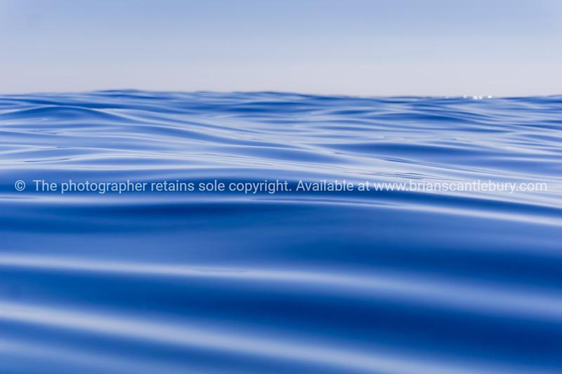Abstract background deep blue ocean motion defocused to horizon