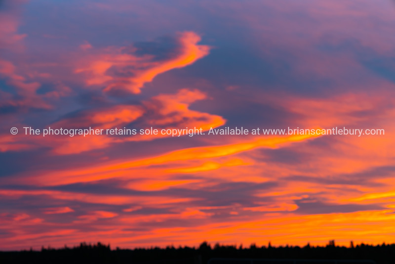 Dramatic bright sunset sky over silhouette rural landscape