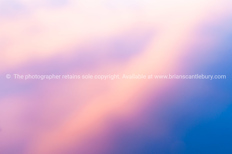 Sunset colored clouds reflecting in calm water, in an abstract background