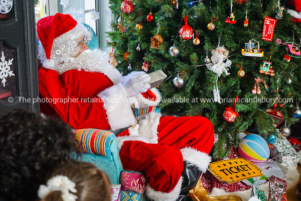 Santa sits by Christmas tree distributing gifts.