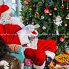 Santa sits by Christmas tree distributing gifts.
