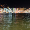 Abstract urban night lights across harbor in zoom blur photographic effect
