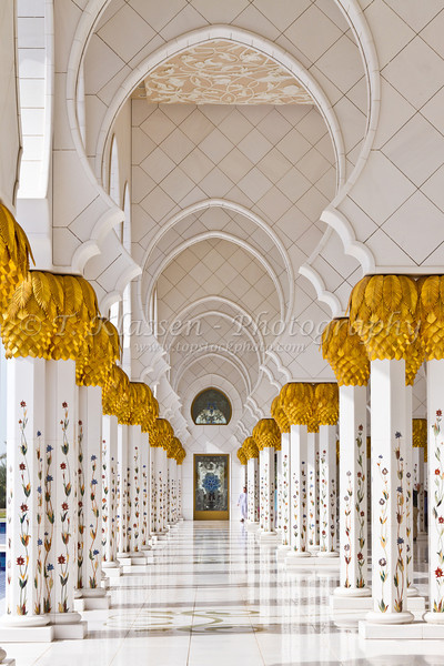 An ornately decorated exterior hallway in the Sheikh Zayed Grand Mosque in Abu Dhabi, United Arab Emirates.