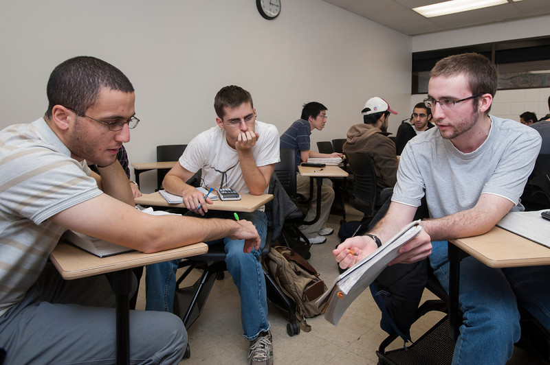 """Professor Amid Jazaeri teaches a Physics class where he """"flipped"""" the instruction format, also called """"Lectures Online Group-work In Class"""" (LOGIC), helping students with homework in class, and assigning video lectures for students to watch outside of class. Photo by Alexis Glenn/Creative Services/George Mason University"""