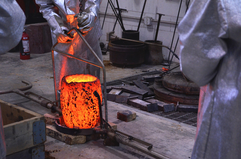 Students pour molten bronze and aluminum into plaster molds in the Boor Sculpture Studio.2013 Professor: Roger Bisbing Photographer: Danielle Dietrich