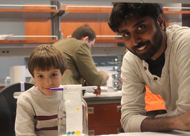 Institute postdoctoral associate Arun Richard Chandrasekaran and Consortium student see result of liquid chromatography experiment.