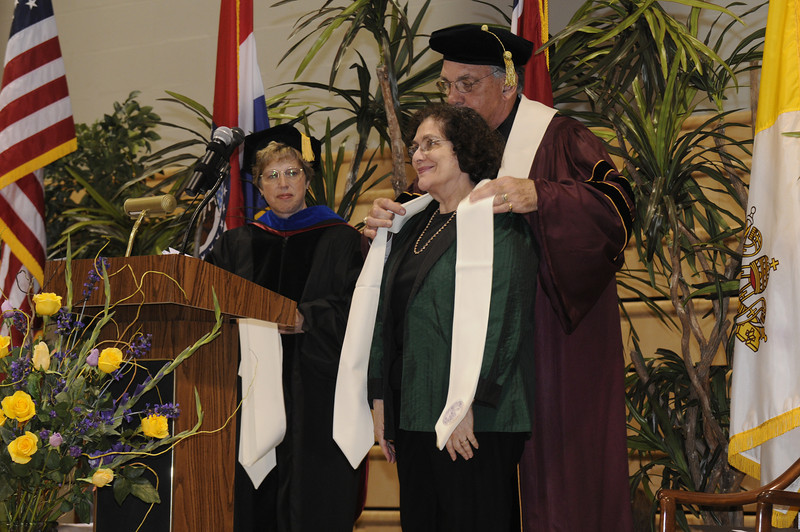Dr. Nancy Golden looks on as Dr. Dennis Golden presents Batya Abramson-Goldstein with a Fontbonne University stole for attending the Convocation.