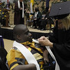 A student recieves his pin for attending a second convocation ceremony.