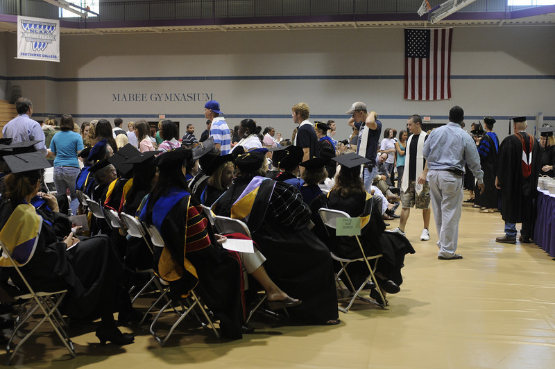 Faculty and staff look on as students recieve pins and stoles.