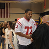 A student smiles and shakes a staff member's hand as he recieves his convocation pin.