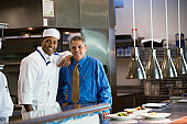 African chef and Hispanic businessmen in kitchen