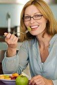Smiling woman eating fruit salad
