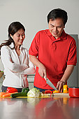 Couple in kitchen, man cutting vegetables, woman watching him