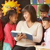 Asian female teacher reading to young students