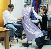 Two teenage boys (12-14) pinning fabric to dressmaker's dummy