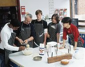 Teenage boys (13-15) in kitchen, one helping teacher with cake mix
