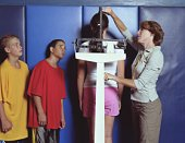 Gym teacher measuring and weighing students (12-14) on scale