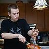 Teenage boy (16-17) carving turkey in kitchen