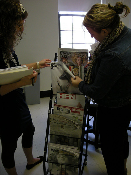 Fashion students selecting periodicals for projects.