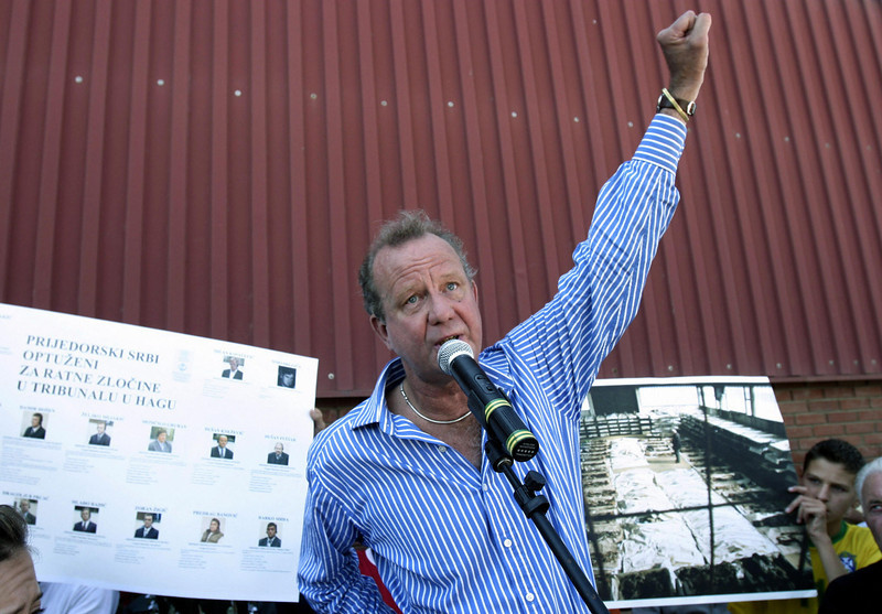 "PRIJEDOR, BOSNIA AND HERCEGOVINA:  Ed Vulliamy, journalist of the British newspaper ""The Guardian"" addresses family members of victims of the torture camp in Omarska near the Western Bosnian town of Prijedor who hold photos of excavated bodies of their relatives, , during a visit to the site of what once used to be the  camp, 06 August, 2006. Photos of the camp and it's prisoners, made in 1992 By the Guardian's Ed Vulliamy, horrified the world's public and drew attention to the fact that ethnic cleansing was being commited at the time in Bosnia, by nationalist forces of Bosnian Serbs. AFP PHOTO STR  (Photo credit should read STR/AFP/Getty Images)"