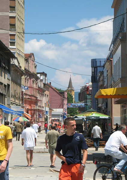 Downtown Prijedor, photographed in the summer of 2007. The new spire of a rebuilt Catholic church is visible in the background.  The original church, built in 1896, was destroyed by Serbs in 1992.   Photograph by Benjamin Moore.