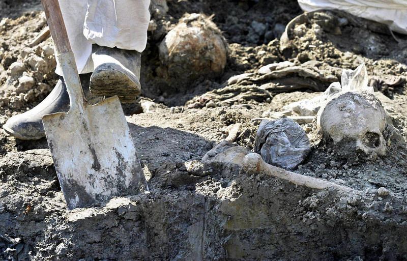 PRIJEDOR, BOSNIA AND HERCEGOVINA:  Forensic experts exhume the remains of 85 Muslim civilians from a mass grave in Kevljani, near Prijedor, some 100 km from Banja Luka 07 September 2004. The civlians are believed to have been inmates of a notorious Serb detention camp from the 1992-95 war, AFP PHOTO STRINGER  (Photo credit should read -/AFP/Getty Images)