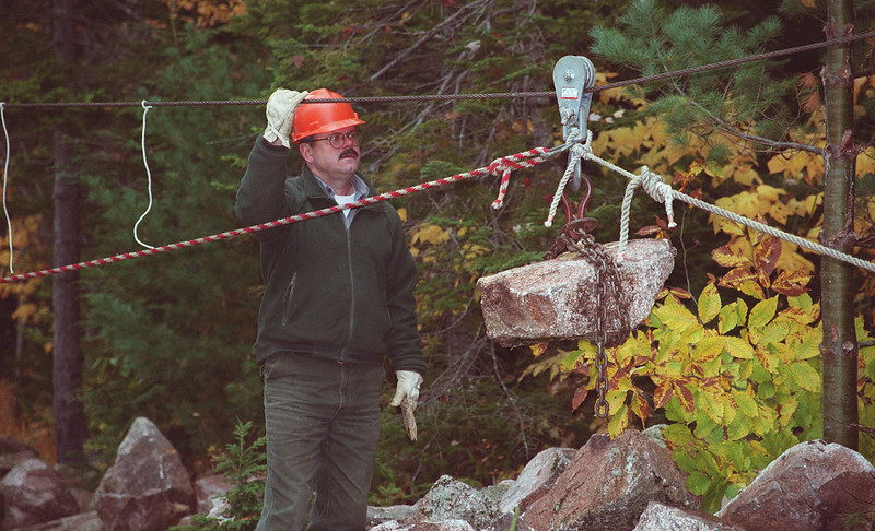 Doug Duncan, a member of the Acadia National Park trails crew, expains the high-line system of wires and pulleys used to fly large chunks of local granite down steep hillsides so they may be used to reconstruct the east leg of the Jordan Pond Loop Trail. The century-old trail is to first to benefit from the park's new Trails Forever mainetanance endowment.<br /> Photo by Misty Edgecomb.  October 20, 2000.  Acadia National Park, Maine.  Bangor Daily News
