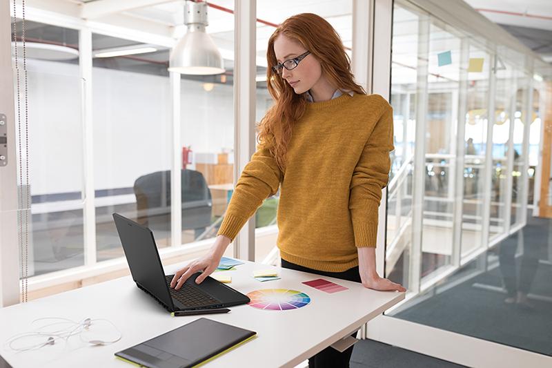 Female graphic designer using laptop in office