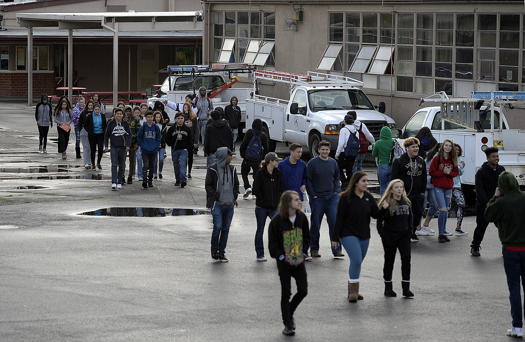 . Vacaville High School students walk to  the quad in front of the English build to honor the memory of  to honor the memory of the 17 people killed at Stoneman Douglas High School last month as they participate in the National School Walkout . Joel Rosenbaum -- The Reporter
