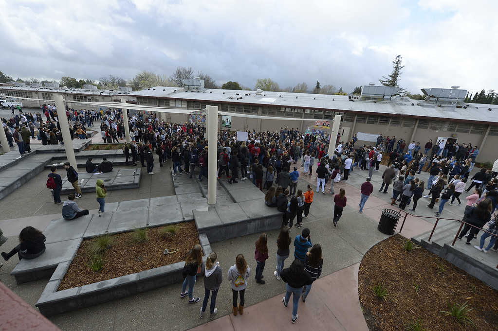 . Vacaville High School students gather in the quad in front of the English build to honor the memory of  to honor the memory of the 17 people killed at Stoneman Douglas High School last month as they participate in the National School Walkout . Joel Rosenbaum -- The Reporter