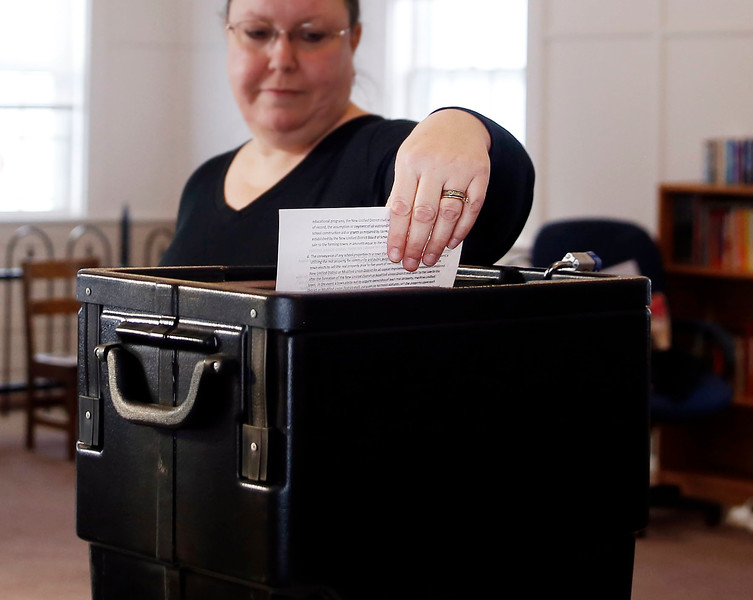 HOLLY PELCZYNSKI - BENNINGTON BANNER Pamela Gahan, of Woodford turns in her vote for Act46 on Tuesday at Woodford town offices.