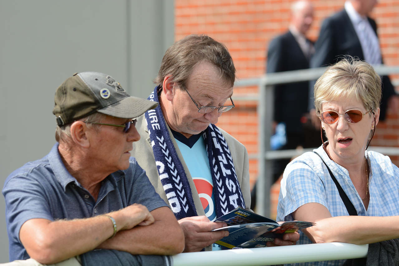 A fan reads the programme before kick off