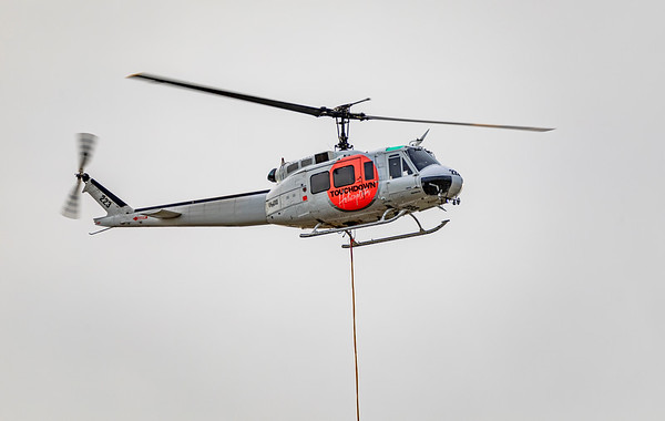 Touchdown Helicopters Bell UH-1H VH-OXE testing it's water bucket at Rockhampton airport