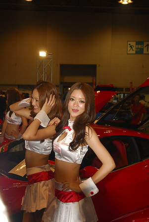 """Race queen"" is a Japanese term for a type of promotional model found as part of a pit crew in certain kinds of motor racing, such as F1 races. They generally wear some sort of revealing costume (mini-dress, swimsuit, hot pants, or the like), as well as pantyhose and high heels or knee-high boots. Race queens who operate in prestigious events and with a large fanbase can also be found at automobile shows purely to draw crowds where they are nearly as important an attraction as the cars or products that they are promoting. There is a magazine dedicated to them called Gals Paradise."