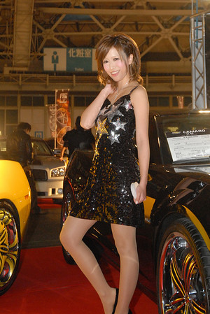 """""""Race queen"""" is a Japanese term for a type of promotional model found as part of a pit crew in certain kinds of motor racing, such as F1 races. They generally wear some sort of revealing costume (mini-dress, swimsuit, hot pants, or the like), as well as pantyhose and high heels or knee-high boots. Race queens who operate in prestigious events and with a large fanbase can also be found at automobile shows purely to draw crowds where they are nearly as important an attraction as the cars or products that they are promoting."""