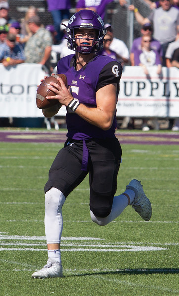 College of Idaho's Jack Rice scrambles outside the pocket looking for an open receiver during game against Carroll on October 2.<br /> by Jim Max