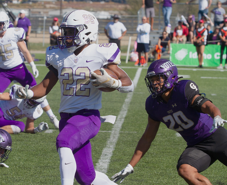 Carroll's 22 looks for open room during game against College of Idaho on October 2.<br /> by Jim Max