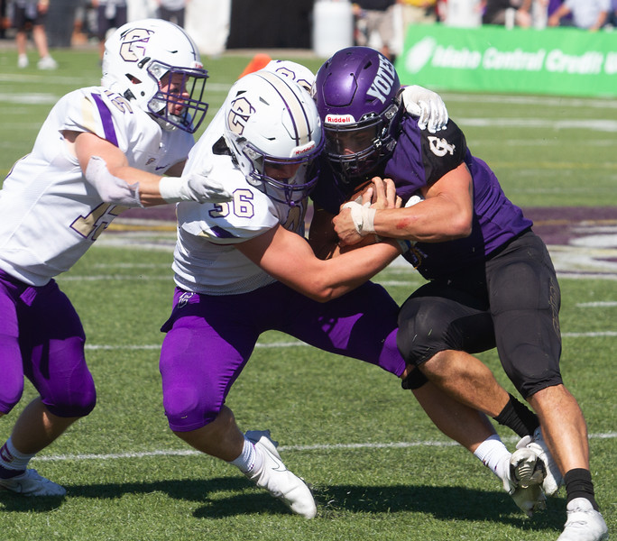 College of Idaho's 42 is tackled by Carroll's Trent Durfey during game on October 2.<br /> by Jim Max