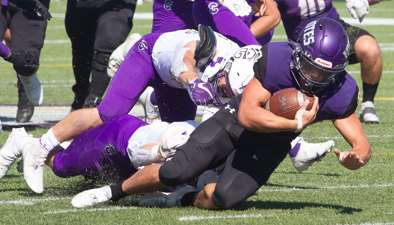 College of Idaho's 42 gets tackled by Carroll defensive players during game on October 2.<br /> by Jim Max