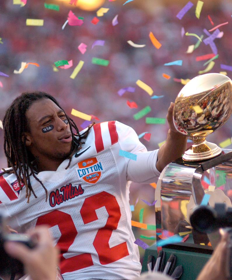 Ole Miss WR Dexter McCluster touches the Cotton Bowl trophy during the celebration after Ole Miss defeated Texas Tech 47- 34 in Dallas Friday.
