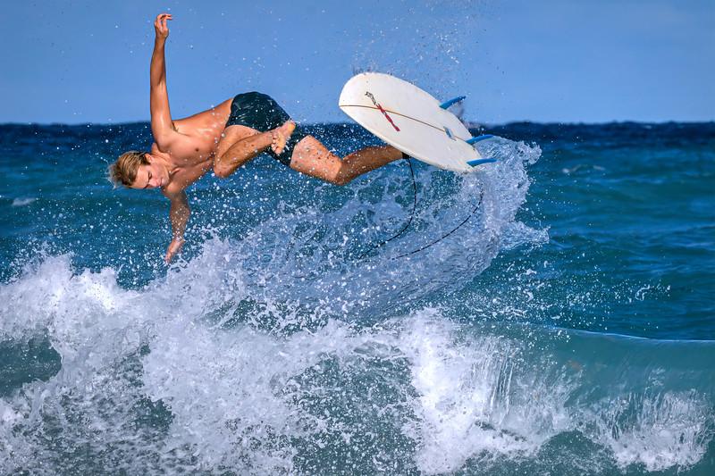 A lone Surfer making a large splash in the wild, windy waves on Palm Beach Municipal Beach, Palm Beach, Florida