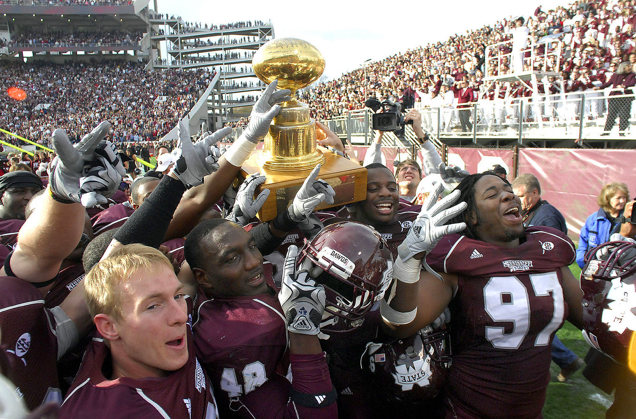Mississippi State players celebrate with the golden egg trophy after defeating Ole Miss Saturday at the Egg Bowl in Starkville.