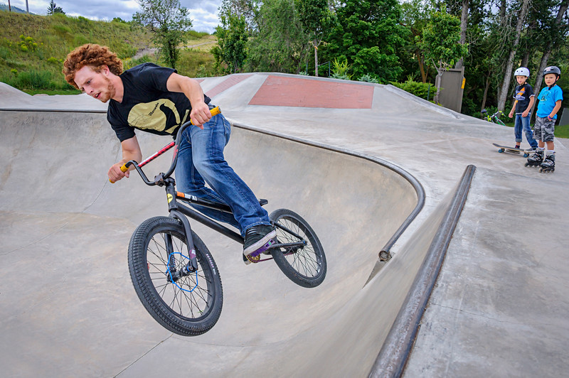 Two kids inspired to greater heights by watching an older bicyclist at Mobash Skate Park in Missoula, Montana